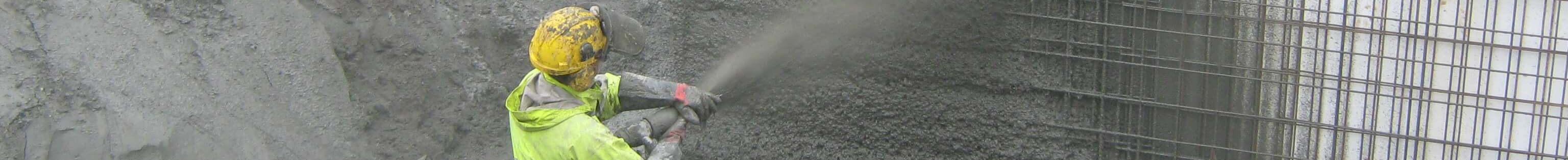 Smalt bilde av mann som sprøyter betong